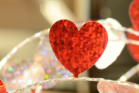 photo of object s: Red flat foil heart on string Close up