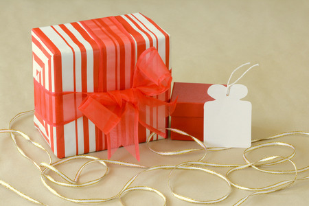 Colorful gift in stripped red and white wrapping paper on\ recycle paper background