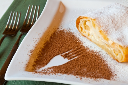 apple strudel on a white plate with fork symbol