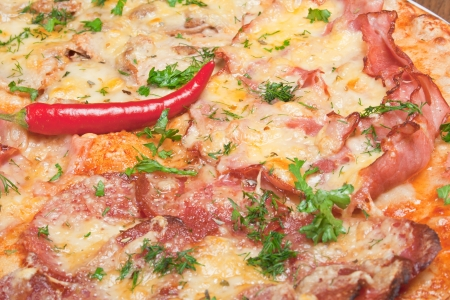 pizza with chili peppers, salami and cheese, close-up