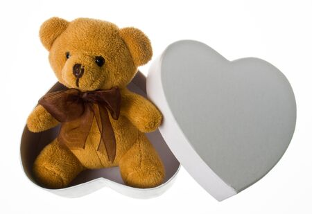 cute little yellow bear with broun ribbon sits in the heart box photo