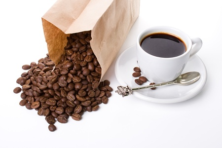 cup of coffee with spoon and a paper packet of coffee beans