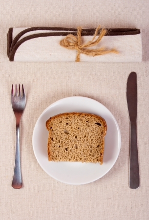 slice of bread on a plate with a fork, knife and napkin on the tablecloth of burlap