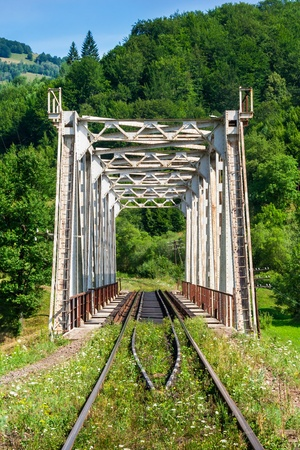 old white rusty metal rail road bridge in mountains