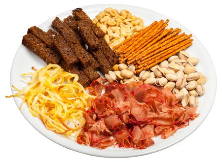 Plate full of crunchy, salty snacks, peanuts, pistachio nut cheese and meat
