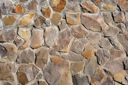 irregular texture of the old yellow stone wall outside Stock Photo