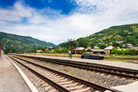 railroad of railway station in countryside which goes through the mountains under blue sky Stock Photo