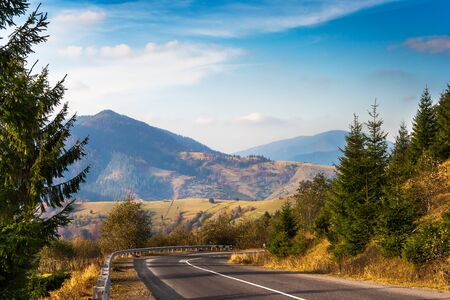 asphalt roadway turning right behind trees going in mountains Stock Photo