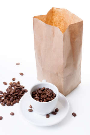 cup on a saucer and a paper bag filled with coffee on a white background