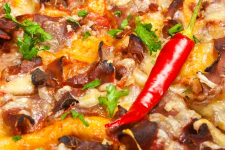 pizza with chili peppers, bacon; salami and cheese, close-up