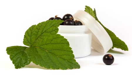 black currants in a jar of makeup with green leaves