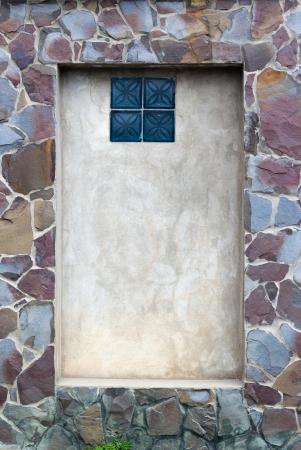 frame in the wall is made of pieces of stone with window inside