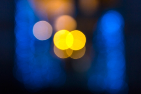 abstract evning blue background of blurred cool lights with warm yellow spot with bokeh effect