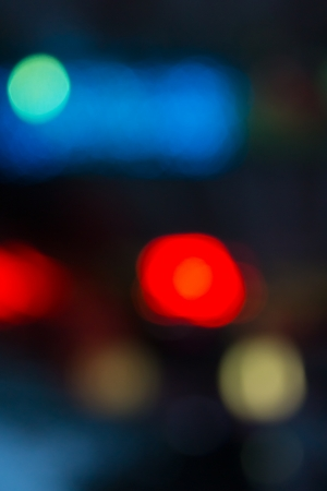 abstract evning blue background of blurred cool lights with red hot spot with bokeh effect