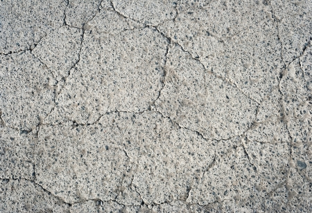 thin fissures and cracks in the gray concrete texture Stock Photo