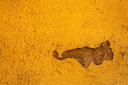 Old yellow with artistic cracked wall with a bummer