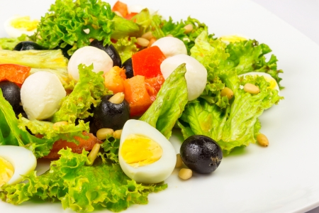 salad with quail eggs, pepper, olives, tomatoes and sesame seeds Stock Photo