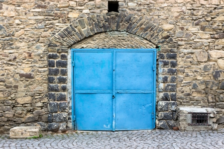 metall: stone wall with arch and blue metall door