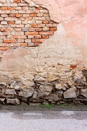 brick wall with chipped plaster, stone foundation and asphalt road Stock Photo