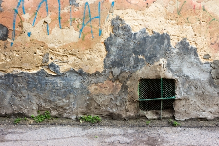 iron window on an old, chipped wall with graffiti on the level of the asphalt road Stock Photo