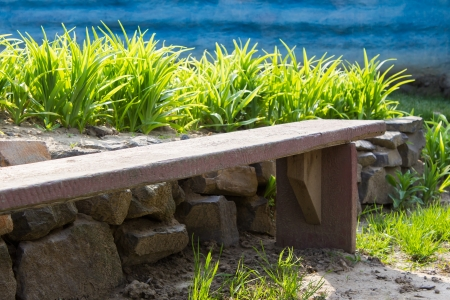 wooden bench on a background of green grass and blue wall