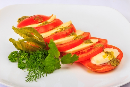 Greek classic summer salad of red big juicy tomatoes cutting circles to 2 millimeters, fresh and soft goat cheese feta sauce of special herbs, served with parsley, dill and fezalis Stock Photo