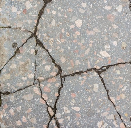 a large number of deep cracks and small scratches in surface of the concrete with granite interspersed
