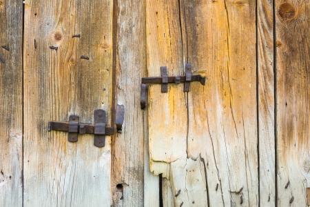vintage wrought metal bars on the texture of broken wooden doors of dilapidated barn
