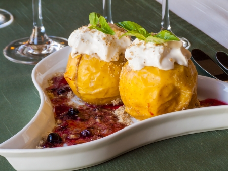 yellow and juicy baked apples with jam, decorated with sour cream and chopped nuts, and mint leaves in a triangular plate