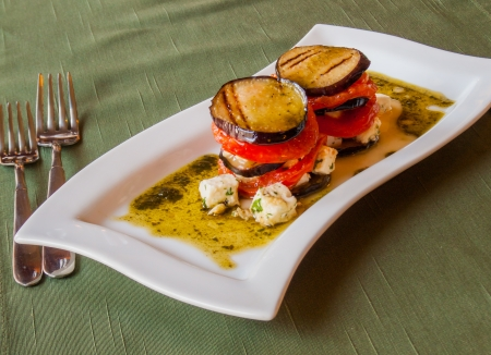 traditional italian crispy grilled eggplant with fresh tomatoes sliced​​, in olive sauce with cubes of Greek feta cheese
