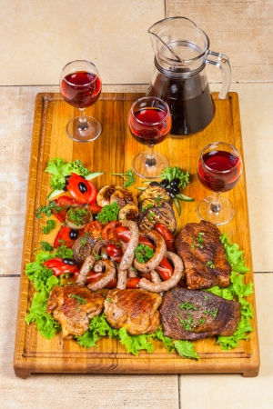 a huge number of all kinds of grilled meat and fried sausages with eggplant and tomato grl, olives and other herbs  Decanter and three glasses of wine on a wooden board
