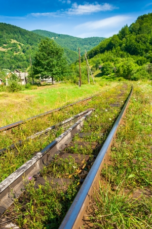 Old railway sneaking through mountain near the populated area Stock Photo