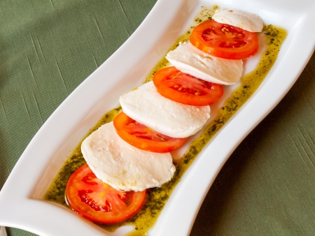 Summer Classic Italian salad  Salad of red juicy tomatoes, fresh and soft mozzarella cheese and sauce
