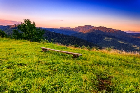 wooden bench on the lawn of the high mountains in the early morning