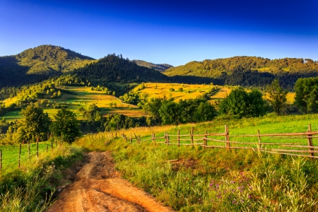The road to the high mountains in the early morning near the wooden fence