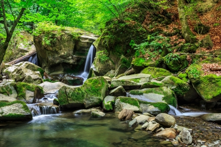 incredibly beautiful and clean little waterfall with several cascades over large stones in the forest comes out of a huge rock covered with moss photo
