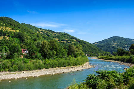 meanders: River meanders through the village at the foot of the mountains Stock Photo