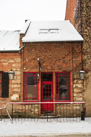 old pub with red windows and a door in winter