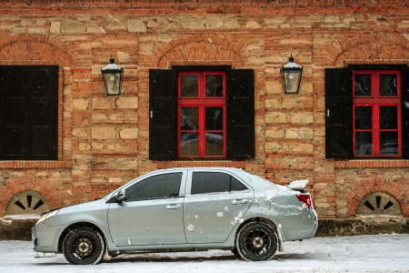 sports car parked near the old building with shuttered windows and lights in winter