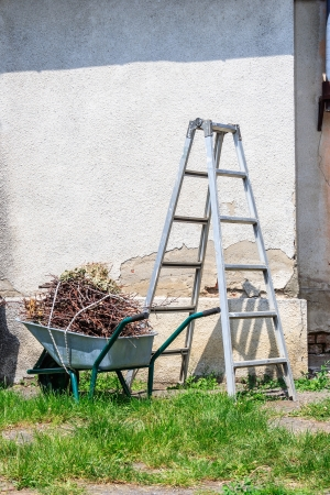 metal ladder and a wheelbarrow filled with cut branches standing in the grass near the old wall