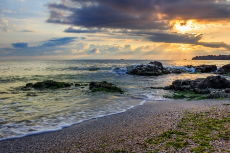 rays of the morning sun behind the clouds illuminate sea and coastal sandy beach with small rocks Stock Photo