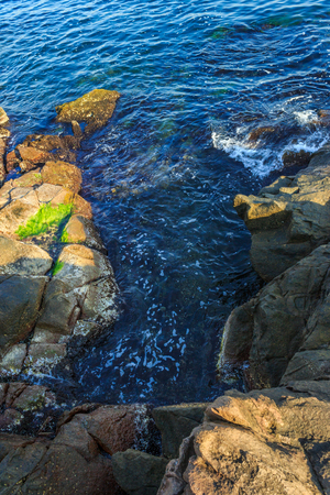 blue sea beating against the coastal jagged cliffs Stock Photo