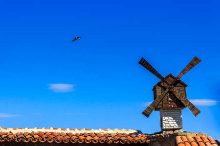 decorative windmill installed at the Architecture building on athe clear sky with a flying seagull