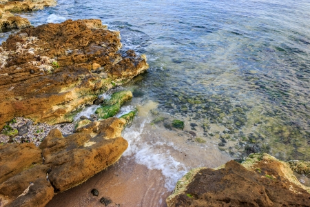 ocean waves breaking on a rocky shore. through the water can be seen seabed. pebbles, shells and seaweed lie on the seabed Stock Photo