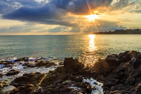 Morning sea landscape with rocky coast, menacing skies, reflections and the rays of the rising sun photo