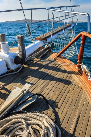 stem deck of a ship, with anchor and rope, walking on the sea towards the island on a sunny day