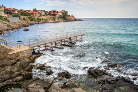 metal pier on the rocky shore near the old sea town Stock Photo