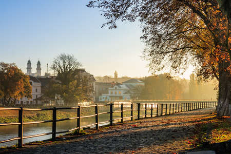 embankment of the old town strewn with foliage and filled with light on autumn morning photo