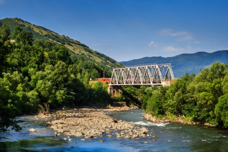 white metal bridge over the river in the mountains on serene summer day