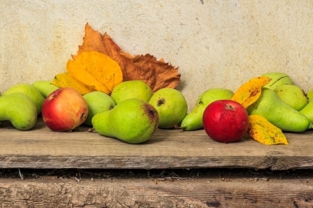 autumnal fruit still life with apples, pears, grapes  leaves on wooden base Stock Photo